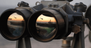A pair of binoculars overlooking a boat and a helicopter.