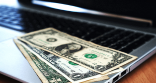 A few dollar bills on top of a laptop.
