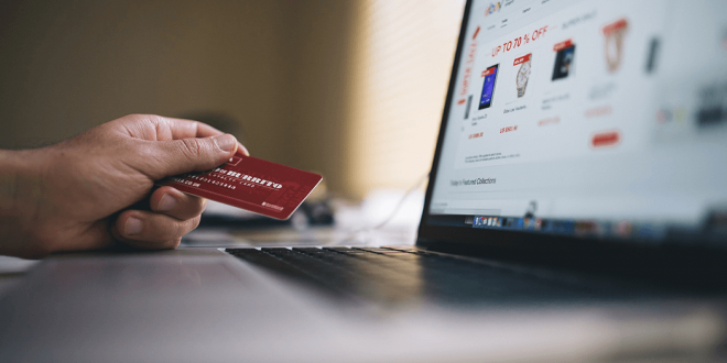 Someone holding a credit card in front of a laptop.