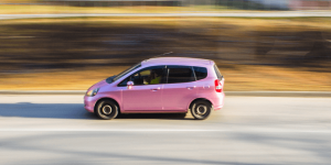 A pink car speeding along a highway.