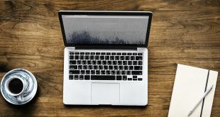 A laptop, a coffee mug, and a notebook.