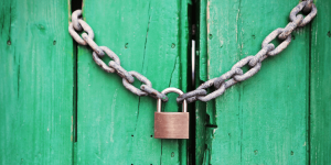 A padlock on a green door.