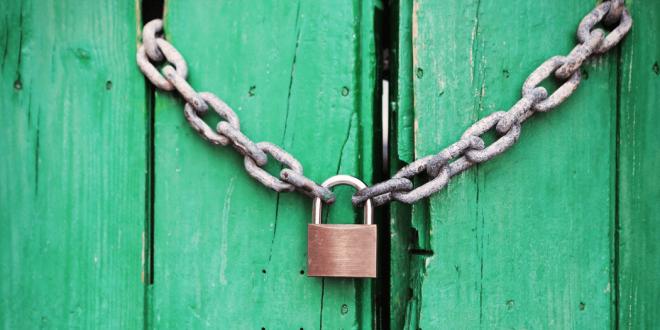 A padlock on a green door.