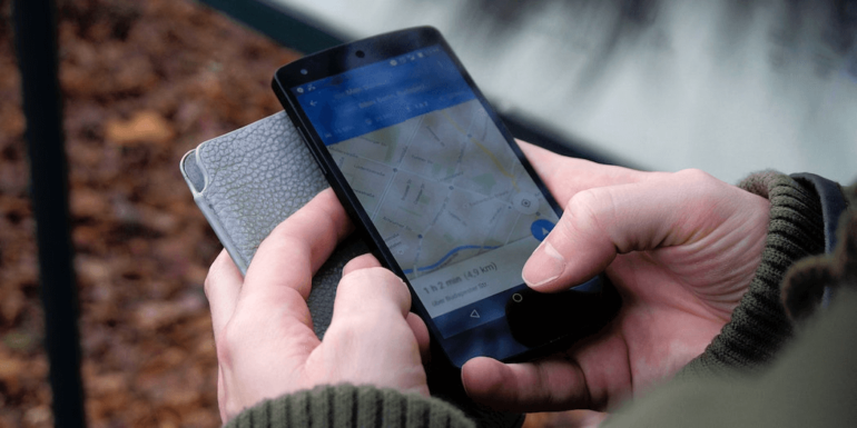 A person holding a phone with a Google map.