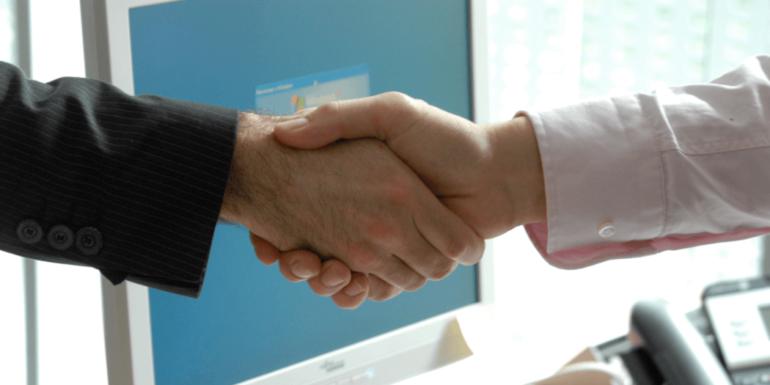 A handshake over a computer.