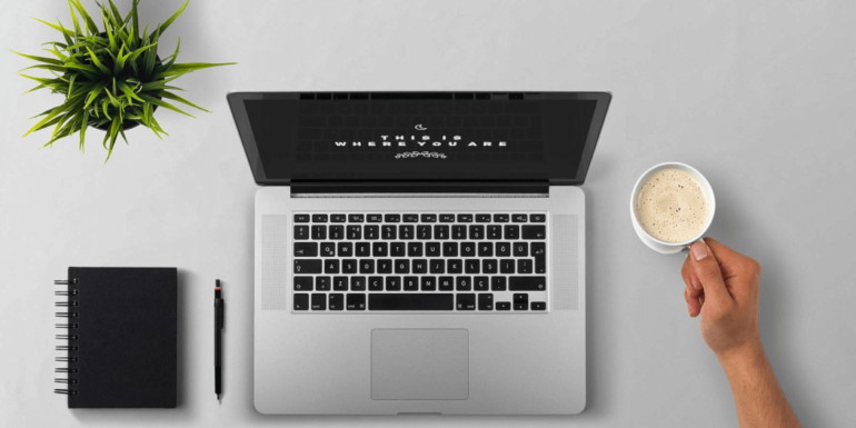 A laptop and a hand holding a cup of coffee.