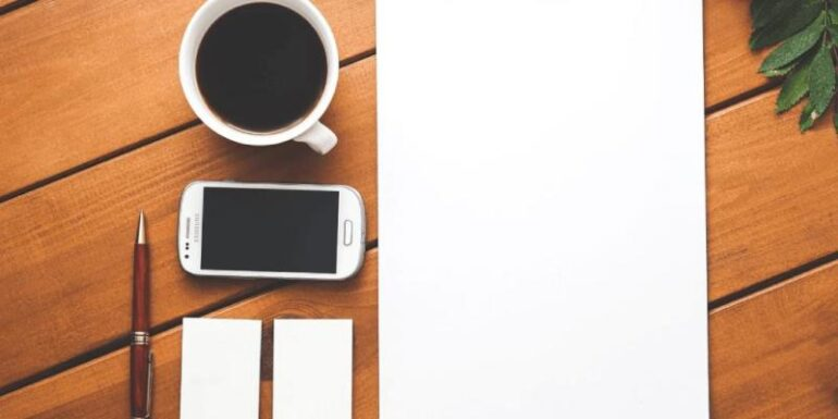 A blank piece of paper next to a phone and a coffee cup.