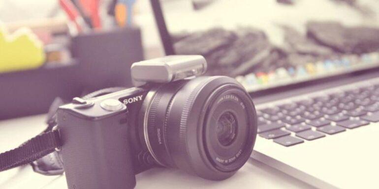 A camera next to a laptop.