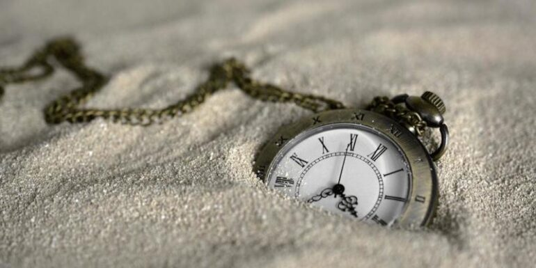 A watch buried in sand.