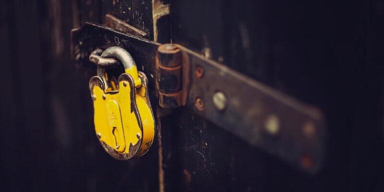 A yellow padlock on a door.