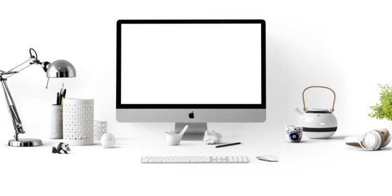 A desktop monitor with a blank white screen sitting on a white desk.