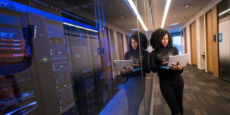 A woman on a laptop leaning against a glass wall with servers behind it.