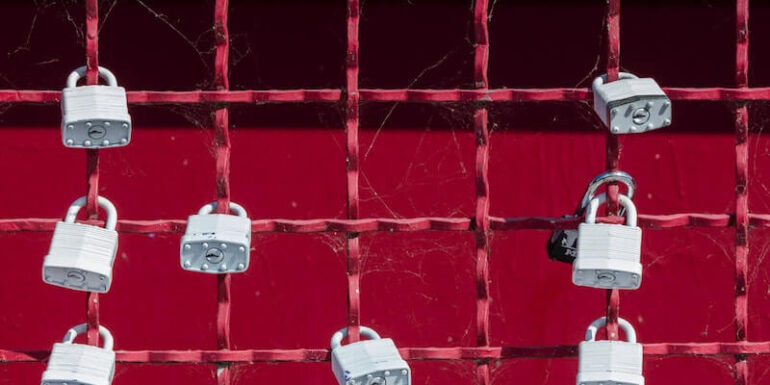 A red gate with white padlocks on it.