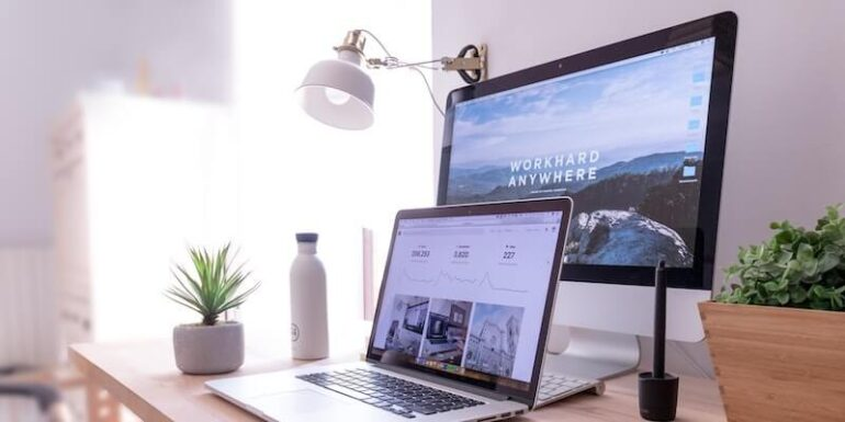 A desktop and a laptop sitting on a desk.