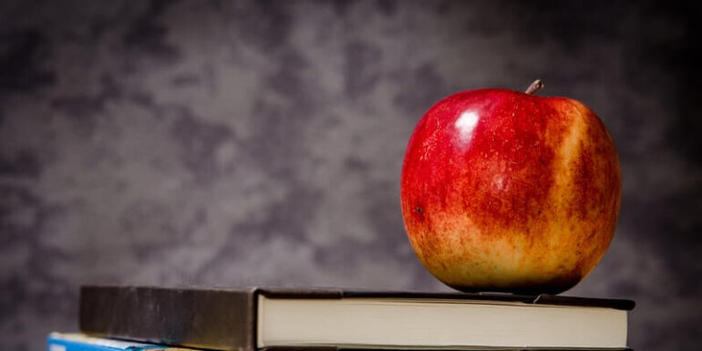 An apple sitting on a textbook.