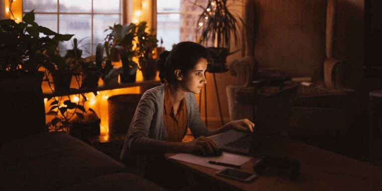 A woman working at home by candlelight.