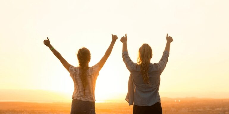 Women standing with their thumbs up at sunset.