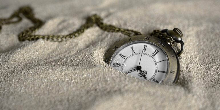 A pocket watch in the sand.
